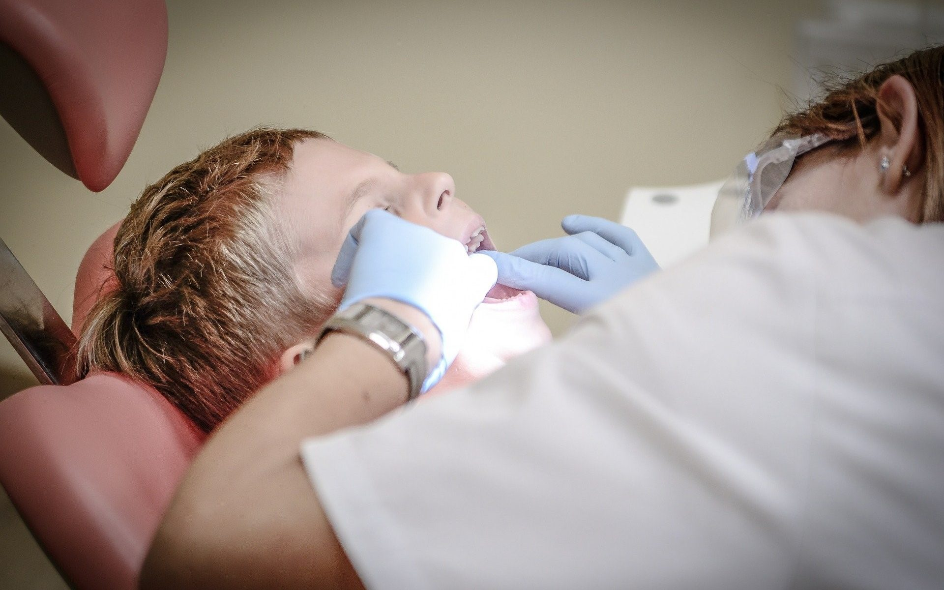 A dentist checking a child's teeth