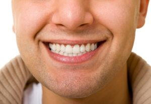 A man smiling with teeth