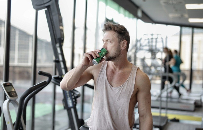 a man drinking energy drink at the gym in the morning