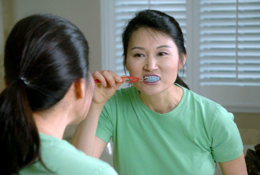 A woman brushing her teeth.