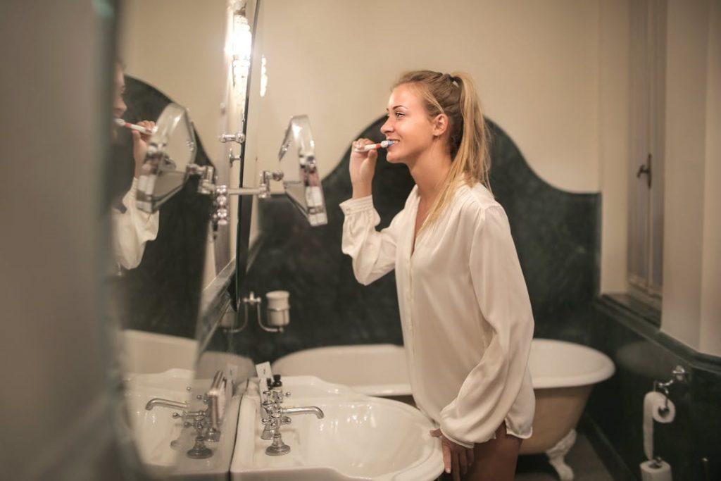 woman brushing her teeth in the bathroom