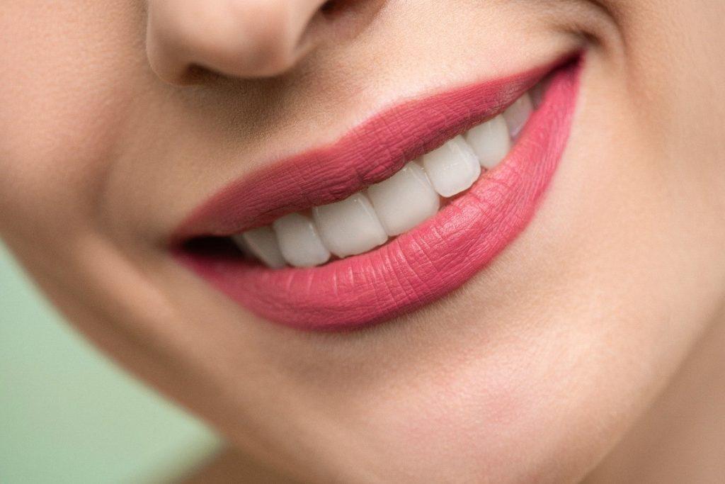 A woman wearing pink lipstick, smiling