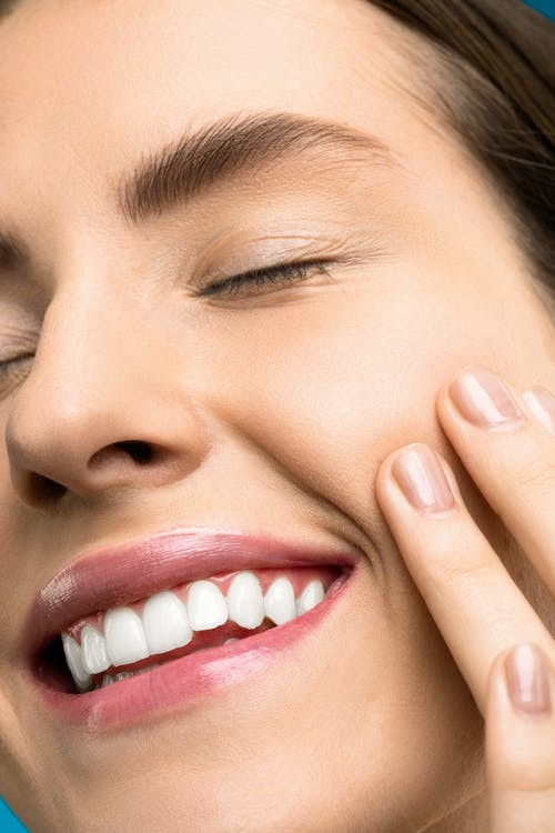 woman with pink lips smiling with her eyes closed in a zoomed-in picture
