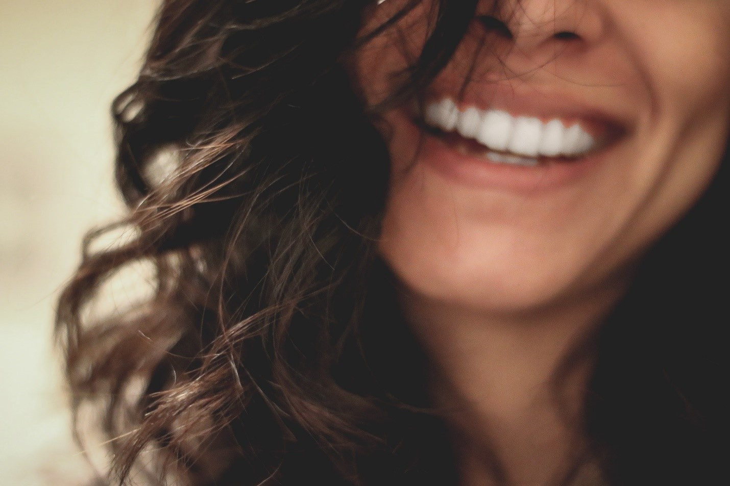A woman smiling and showing white teeth