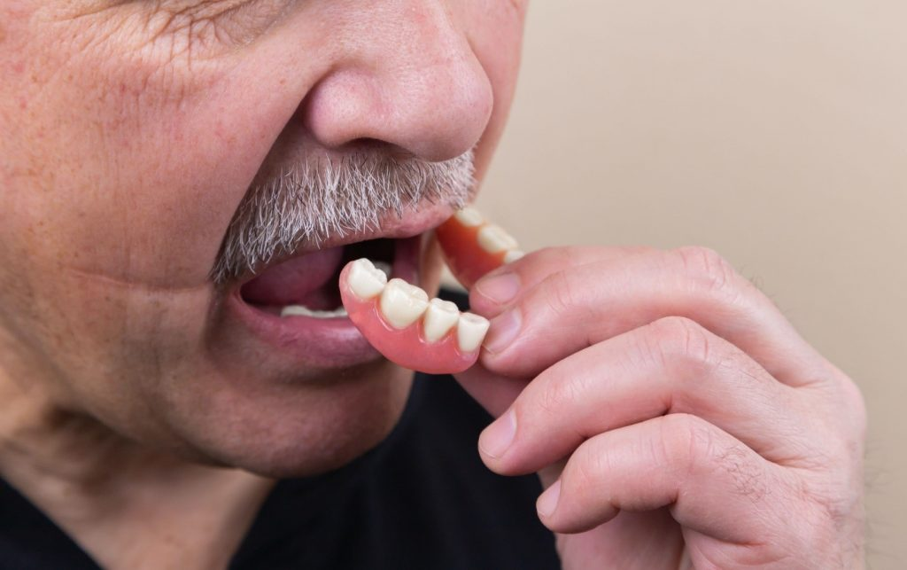 A person fitting denture inside their mouth