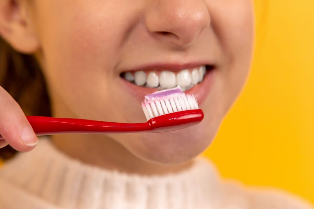 A person with a toothbrush and toothpaste