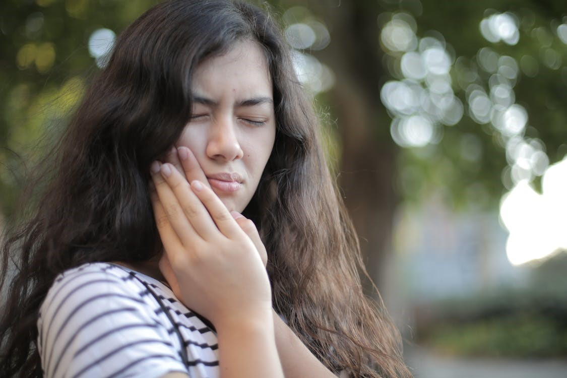 A girl with a hand on her face because of a toothache.