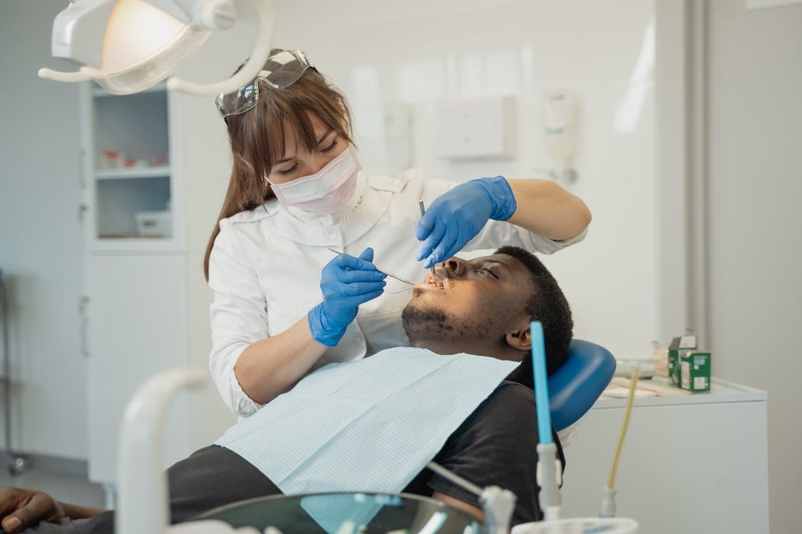 A dentist is treating the patient using a sedation technique.