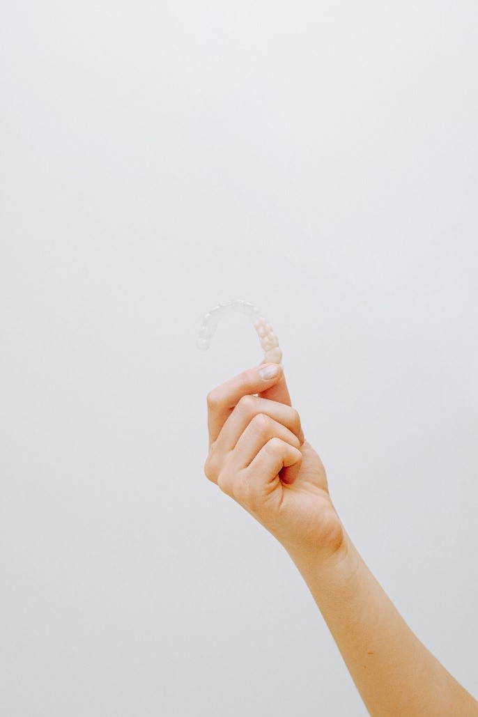 a hand holding clear aligners